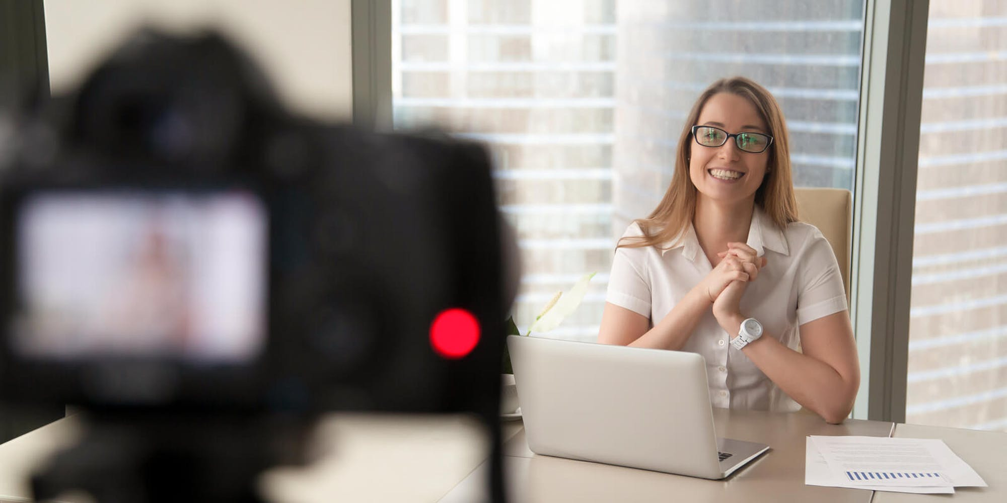 A woman filming a video of herself speaking at a desk
