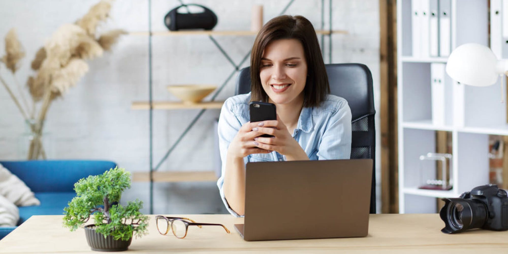 A woman smiling at her phone in her office