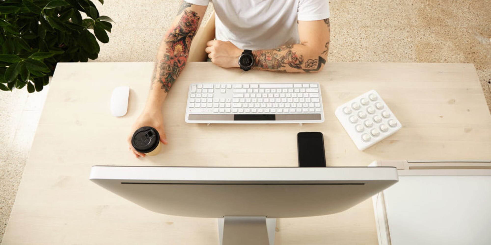 Top down view of a person using an imac and apple keyboard while holding on a cup of coffee