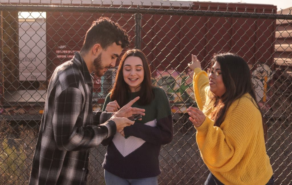 3 teenagers standing next to a wire fence, having fun