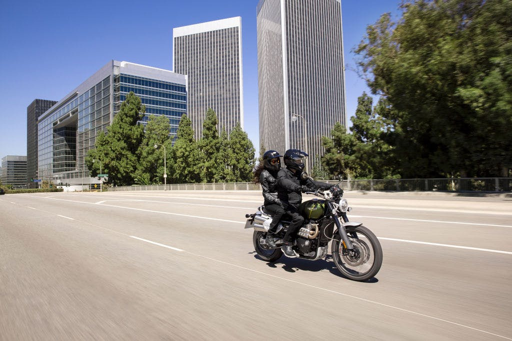 TRIUMPH SCRAMBLER 1200XC being ridden on the road with a passenger