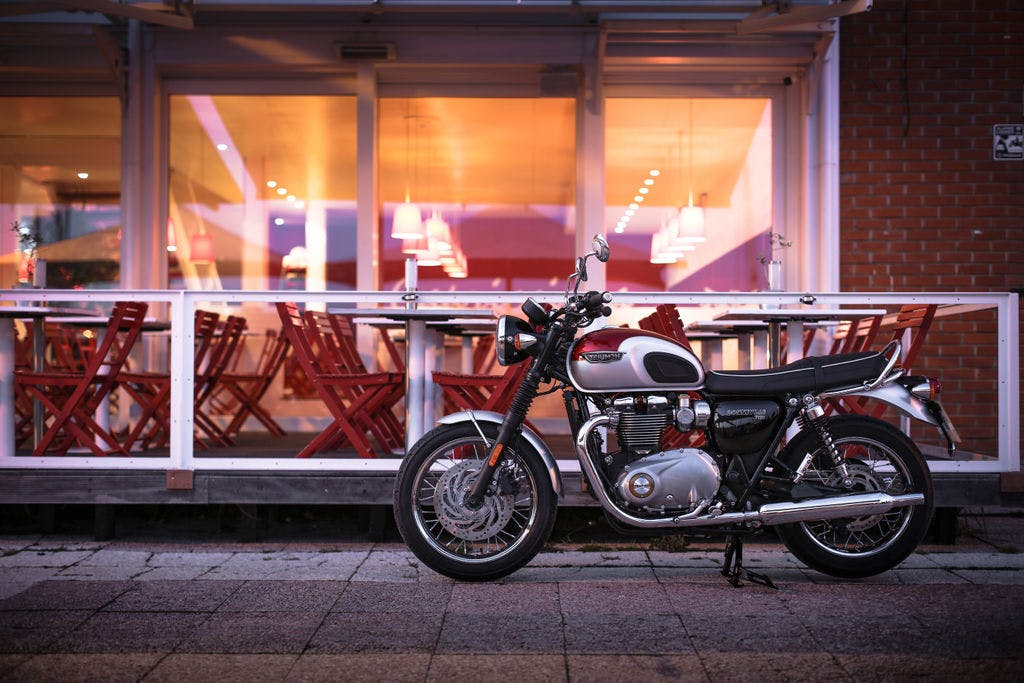 TRIUMPH BONNEVILLE T120 in cranberry red and aluminium silver colour, parked