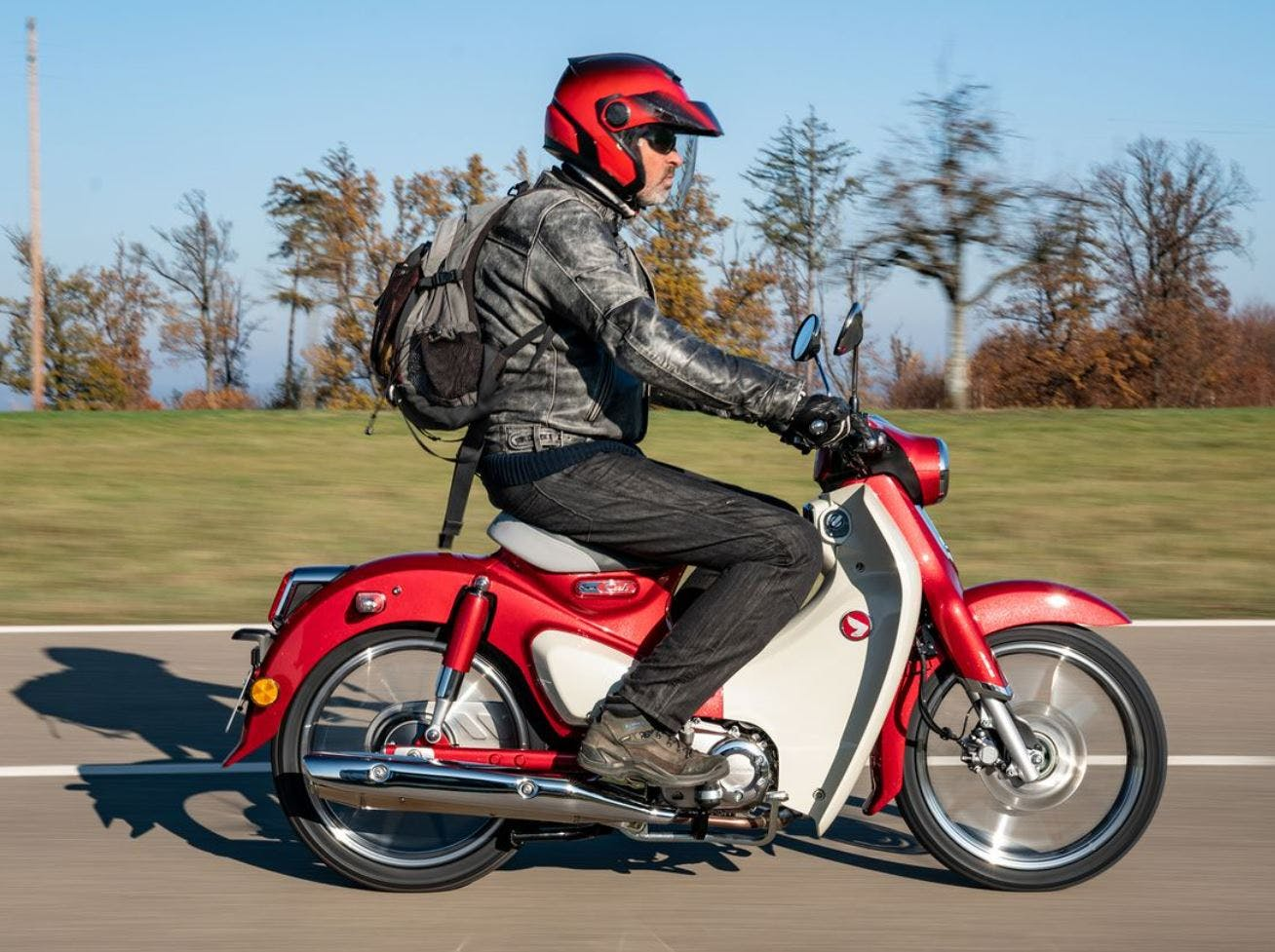 Honda C125 Super Cub in Pearl Nebula Red colour being ridden on the road