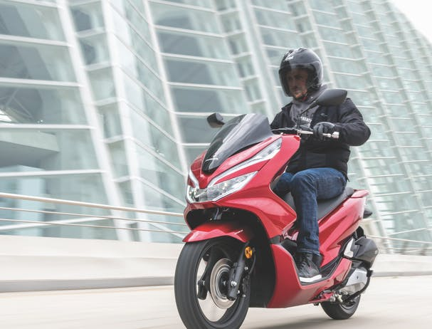Honda PCX150 in candy lustre red colour on the road