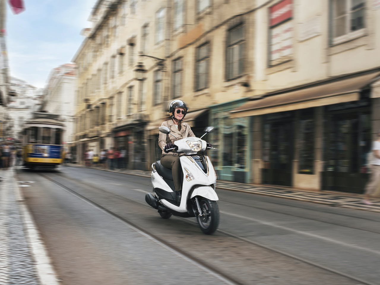 Yamaha D'elight 125 scooter in Milky White riding down city street