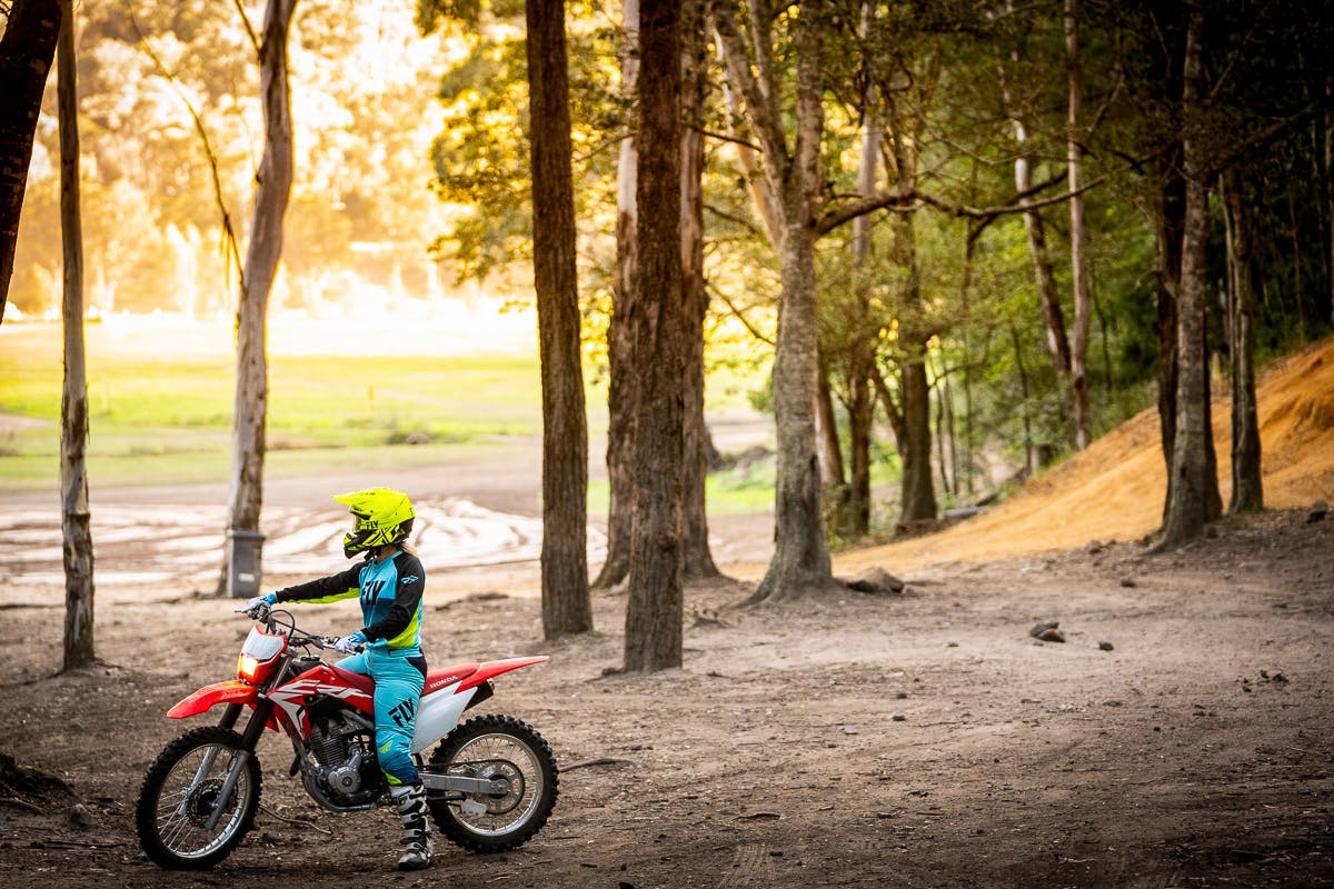 Honda CRF250F in extreme red colour being ridden on off road track