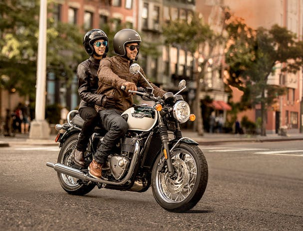 TRIUMPH BONNEVILLE T120 being ridden on the road with a passenger