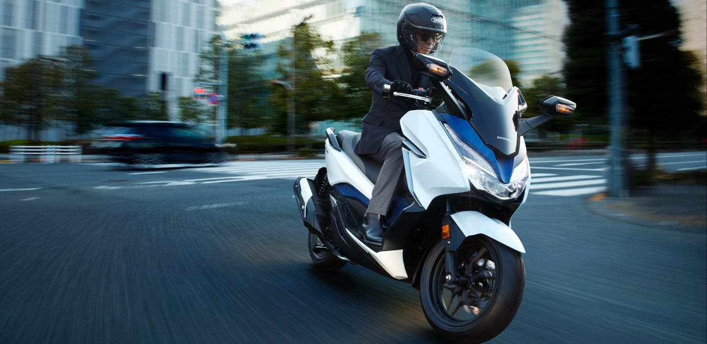 Honda Forza 300 in Pearl Horizon White colour being ridden on the road