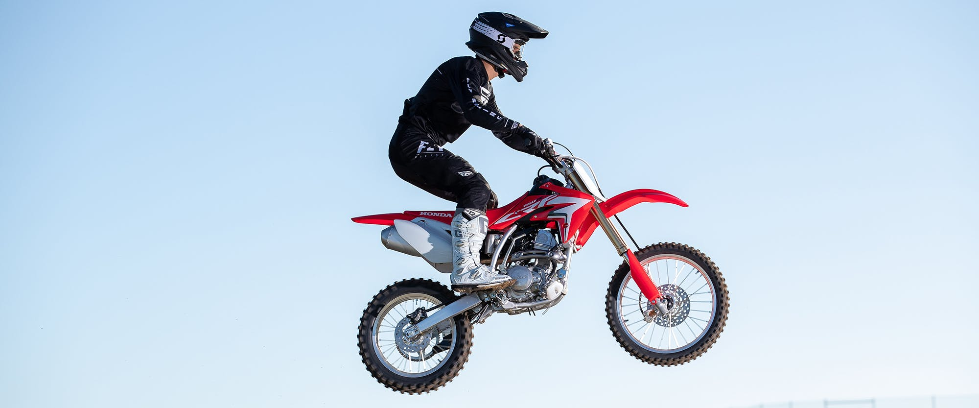 Honda CRF150R in extreme red doing air stunts