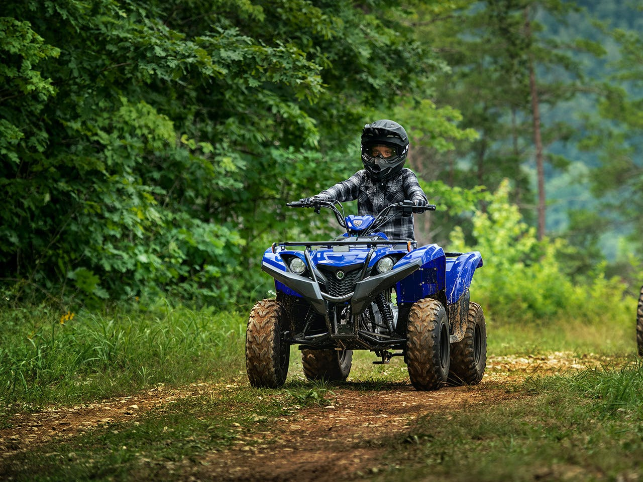 Yamaha Grizzly 90 in Steel Blue colour, being ridden off-track
