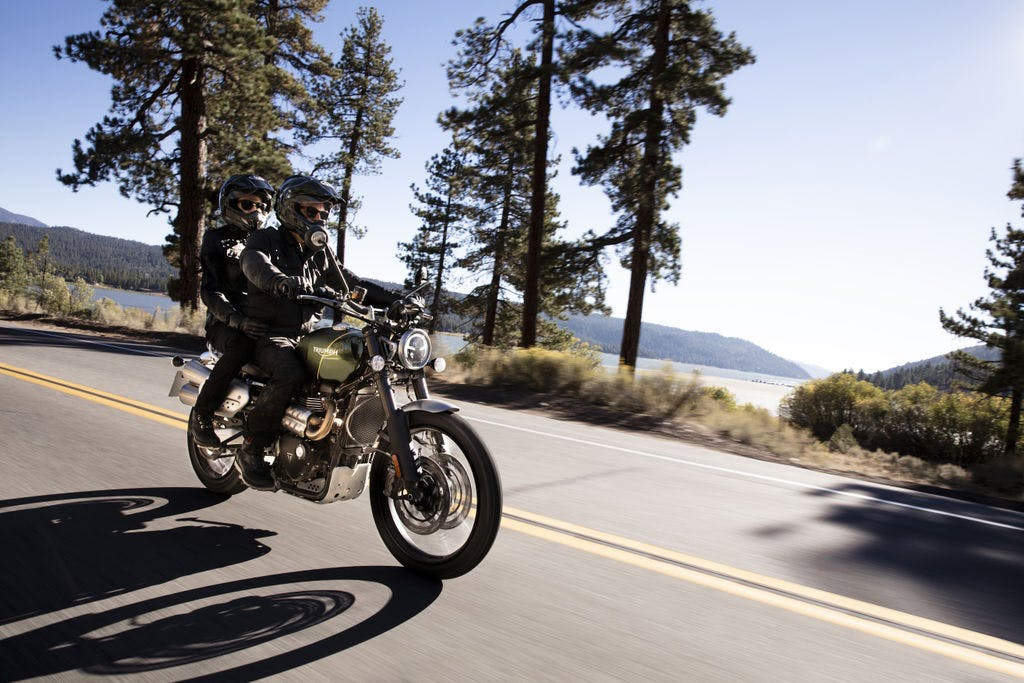 TRIUMPH SCRAMBLER 1200XC being ridden on the hill road with a passenger