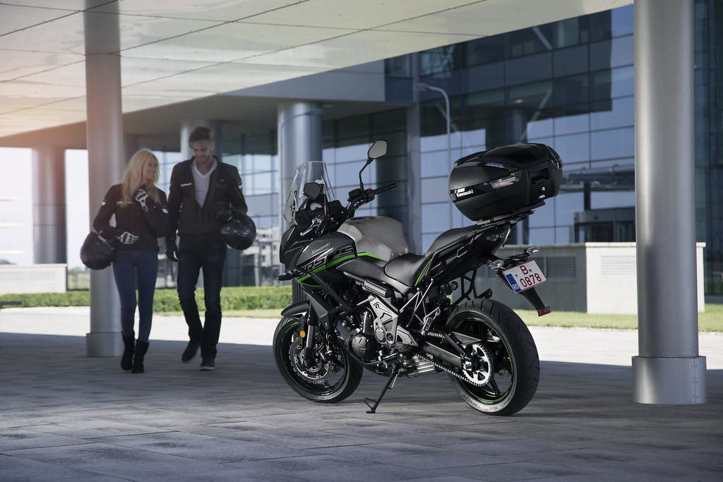 KAWASAKI VERSYS 650L in metallic flat spark black and metallic carbon grey colour, parked with two riders