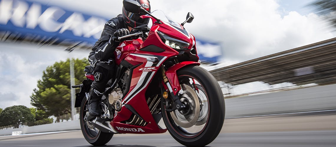 Honda CBR650R in grand prix red colour, being ridden on a race track