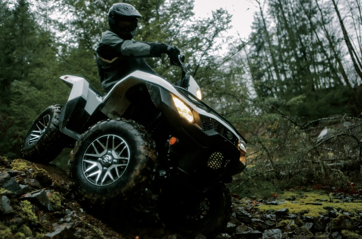 SUZUKI KINGQUAD 750AXI 4x4 PS SE BEING RIDDEN ON A FOREST