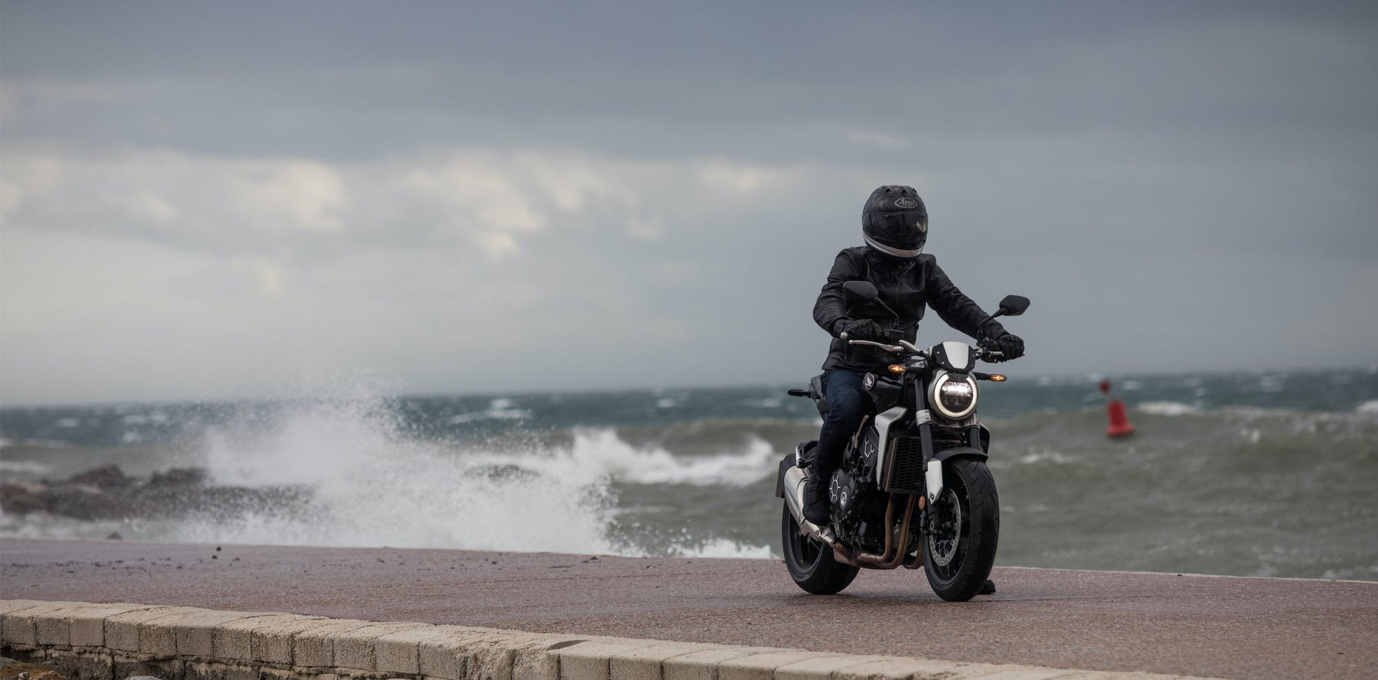 Honda CB1000R in graphite black colour, being ridden on the street road by the bay