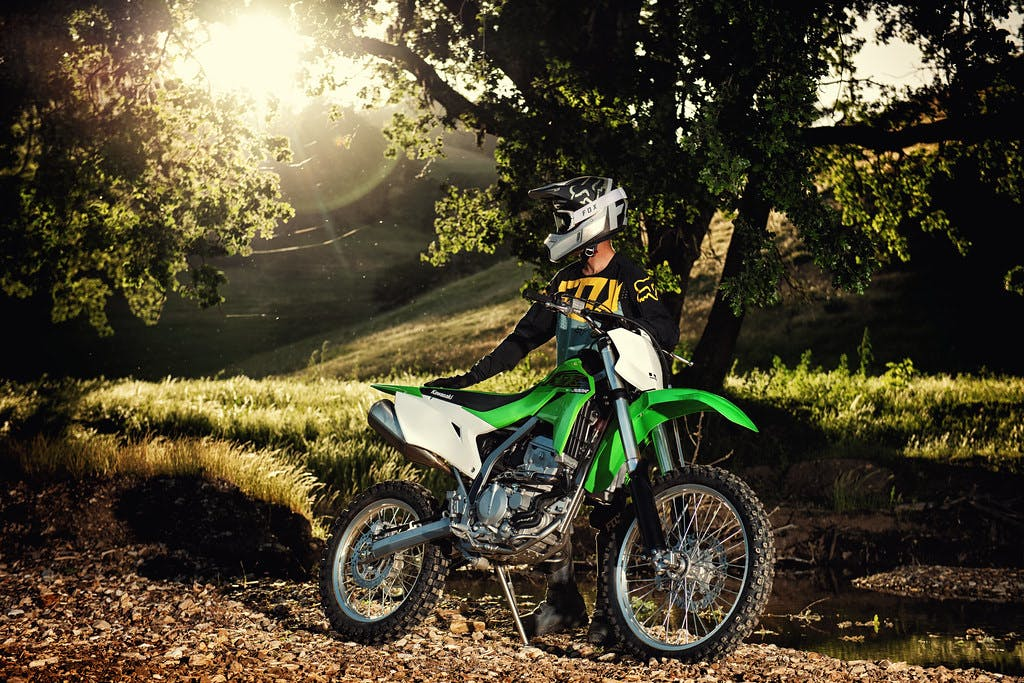 Kawasaki KLX300R parked in a forest road