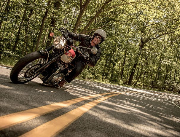 TRIUMPH THE BONNEVILLE T100 being ridden on the road