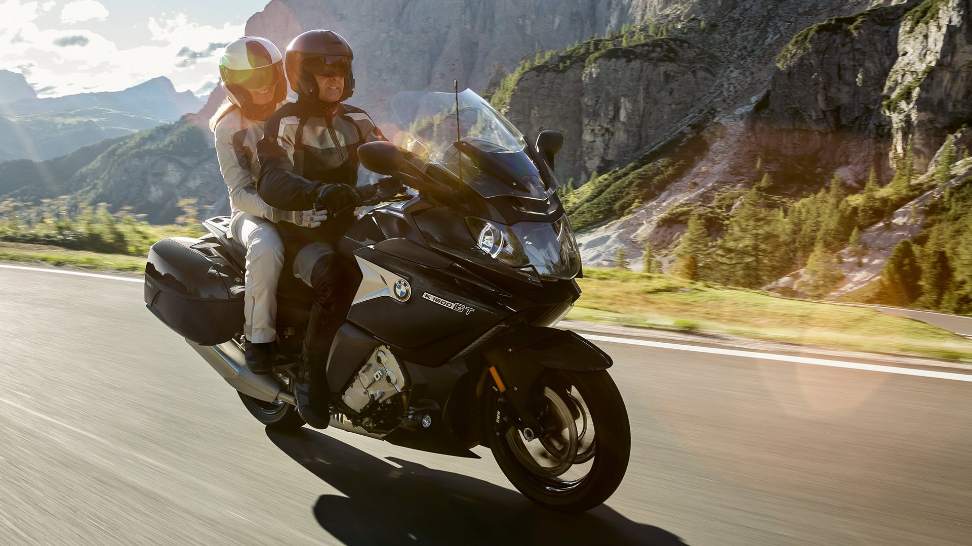 BMW K 1600 GT being ridden on the hill road with a passenger