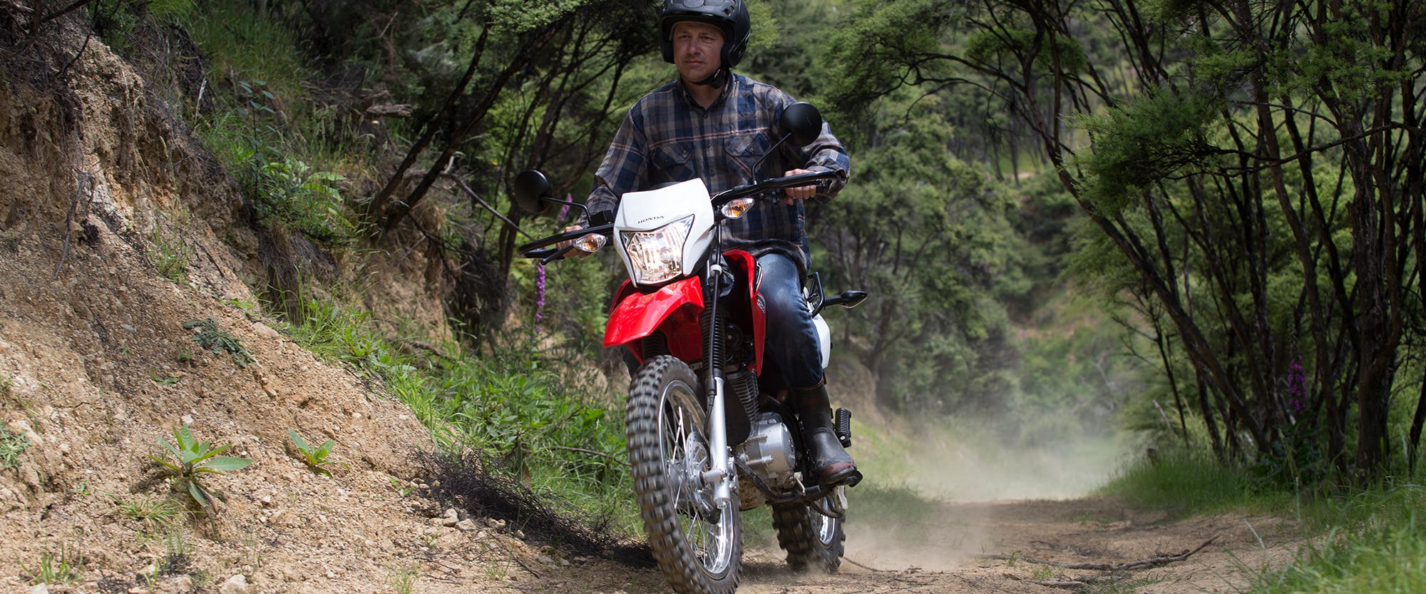 Honda XR150L in fighting red colour being ridden on off-road track