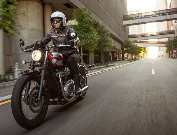TRIUMPH BONNEVILLE BOBBER BLACK being ridden on the road