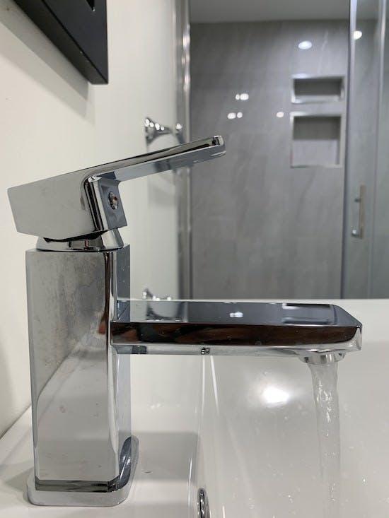 Renovated basement bathroom faucet closeup