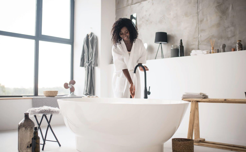 Femme coulant un bain dans une salle de bains rénovée
