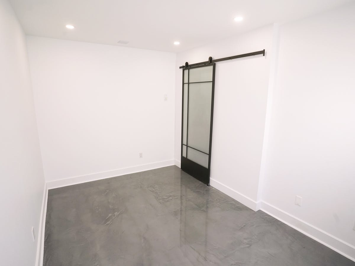 Renovated basement office with French frosted barn door