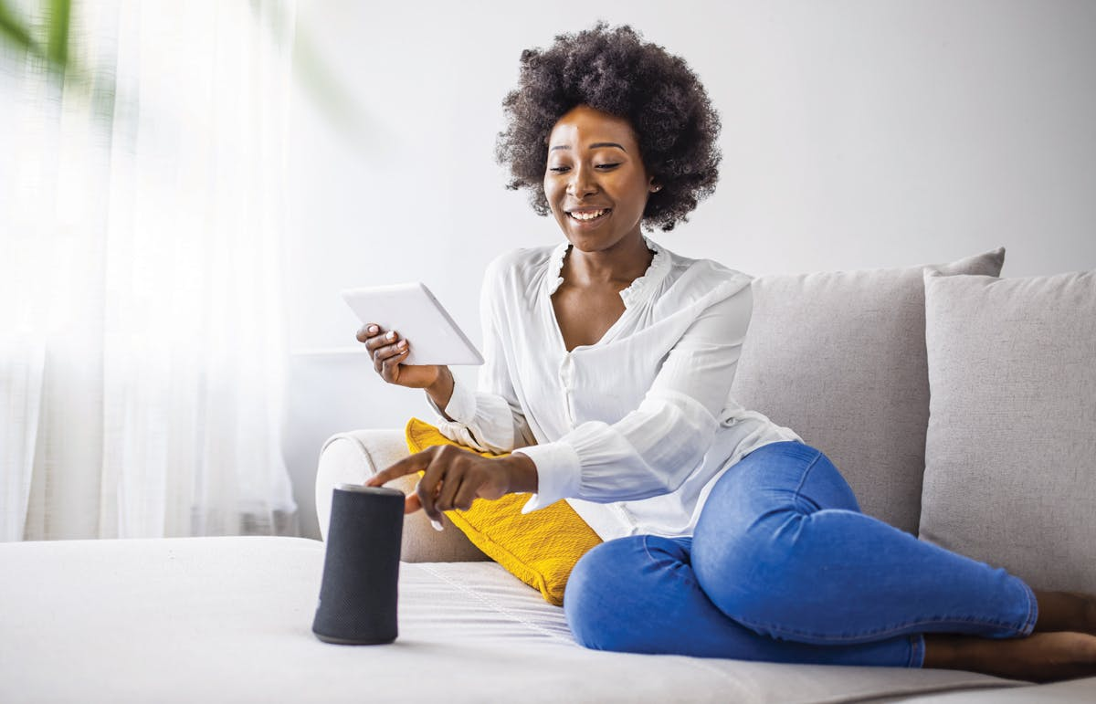 Woman sitting on couch playing music on smart speaker