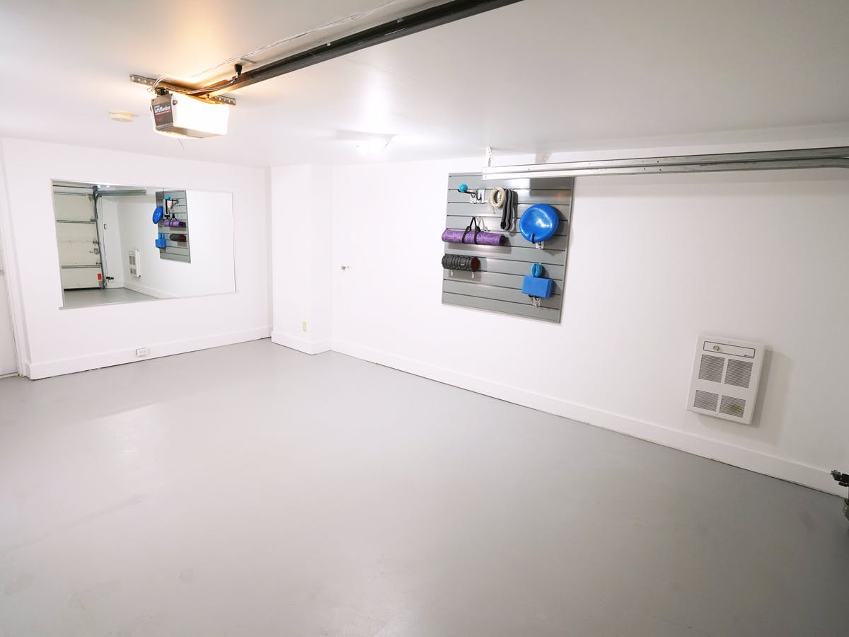 Renovated garage with workout equipment on wall
