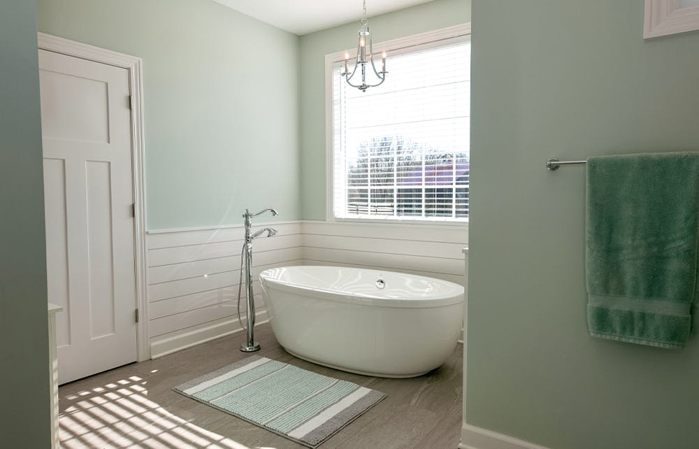 Renovated bathroom with chandelier over bathtub