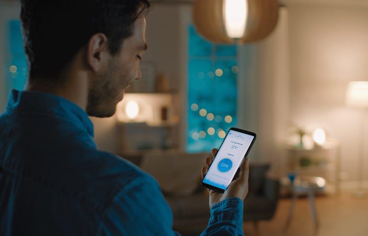 A man adjusting his home lighting on his mobile device