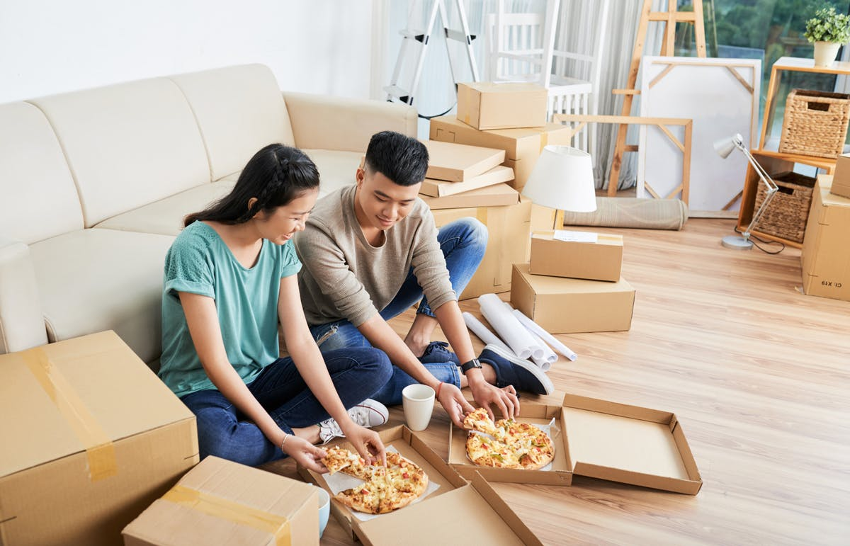 Eating pizza surrounded by boxes