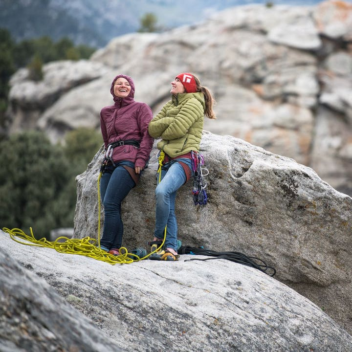 Photograph by Andy Earl of Babsi Zangerl and Hazel Findlay leaning on a boulder outdoors