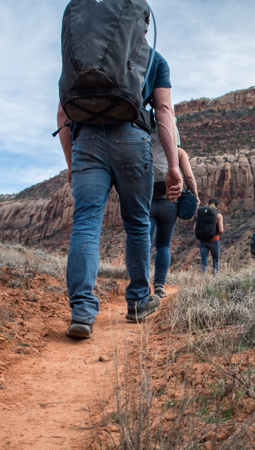 A group of people wearing Forged Denim pants approach a crag in the desert