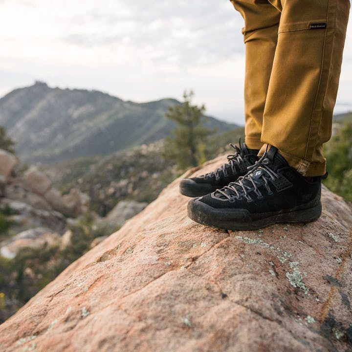 Photograph by Christian Adam feature a person's feet standing on a boulder