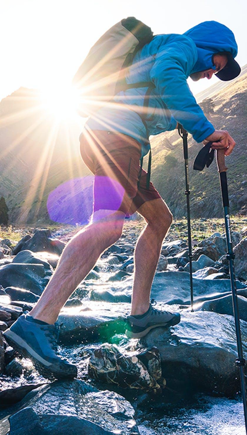 man crossing a mountain creek