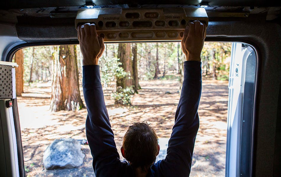 Alex Honnold hangboards in his van while checking out the scenery outside.