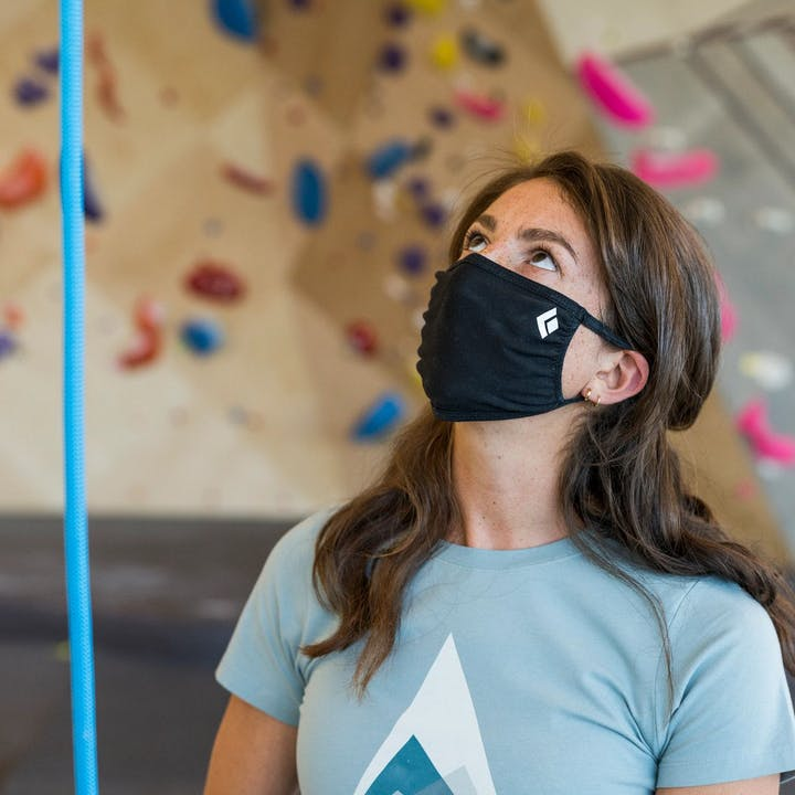 Photograph by Christian Adam of a woman belaying with a face mask