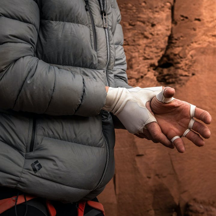 Photograph by Andy Earl of woman putting on crack gloves in the desert
