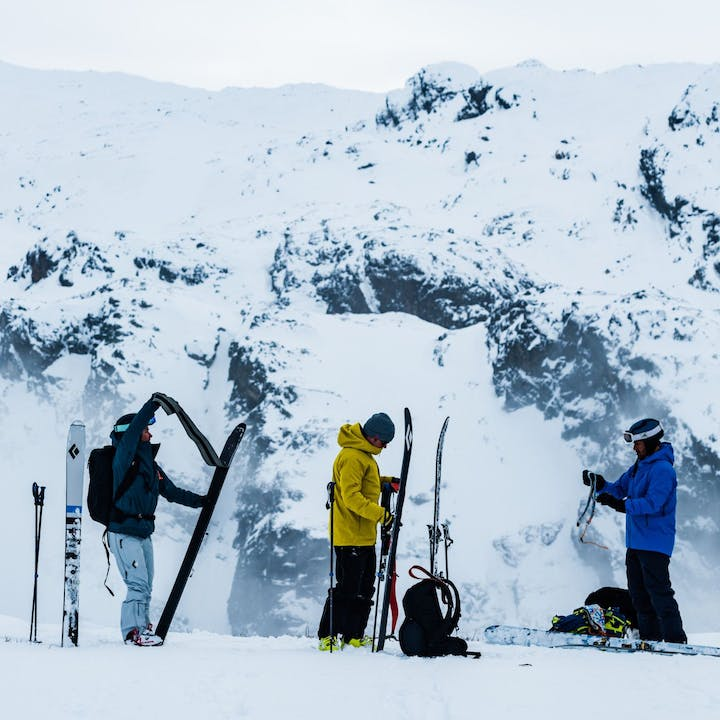 Photograph by Mattias Fredriksson of three people preparing to ski outside.