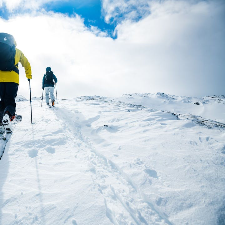 Photograph by Mattias Fredriksson of two people skinning up a mountain