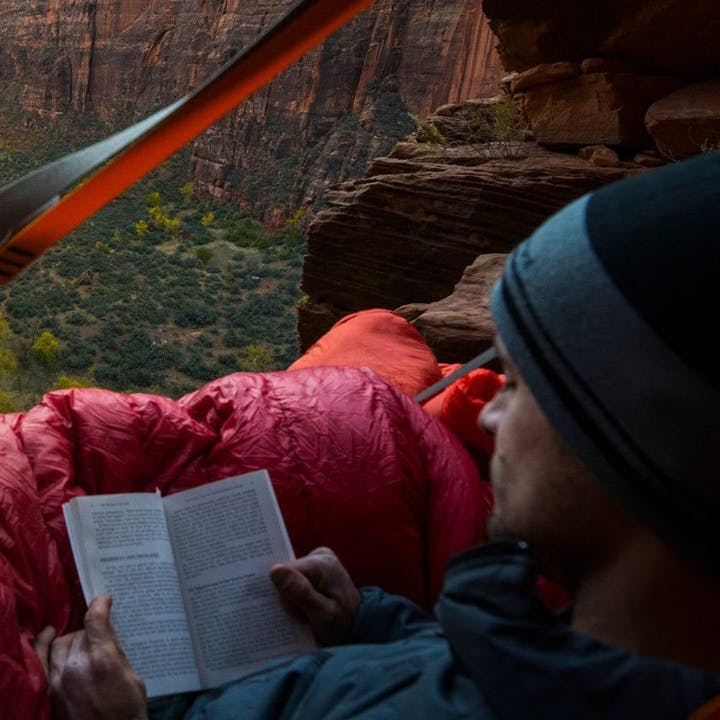 Photograph by Andy Earl of a man reading a book on a portaledge in Zion