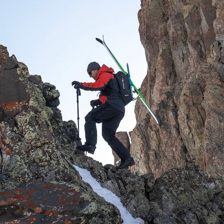 Photograph by Jeff Cricco of man hiking across a ridge with skis strapped to his pack