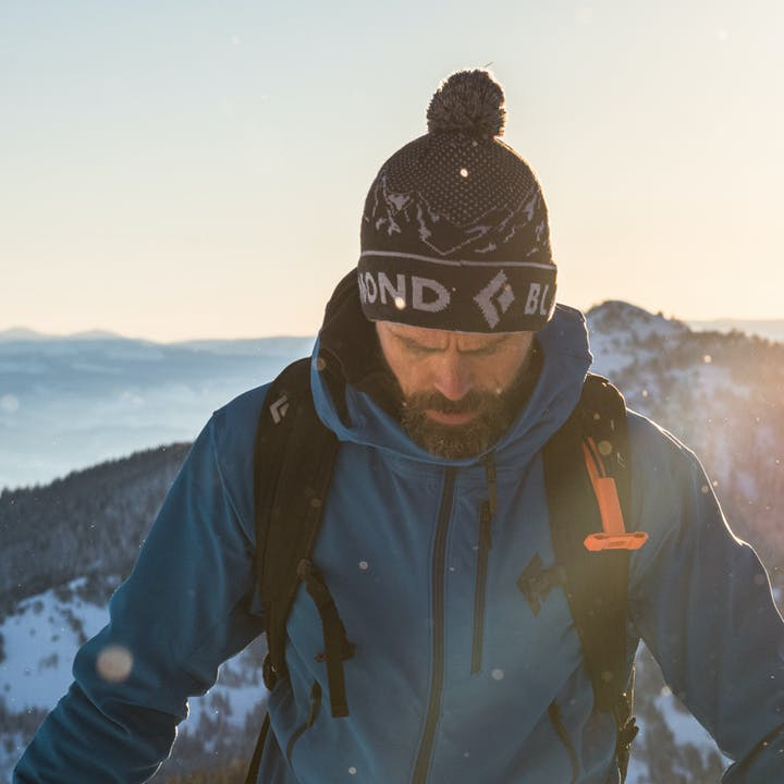man wearing black diamond beanie while backcountry skiing