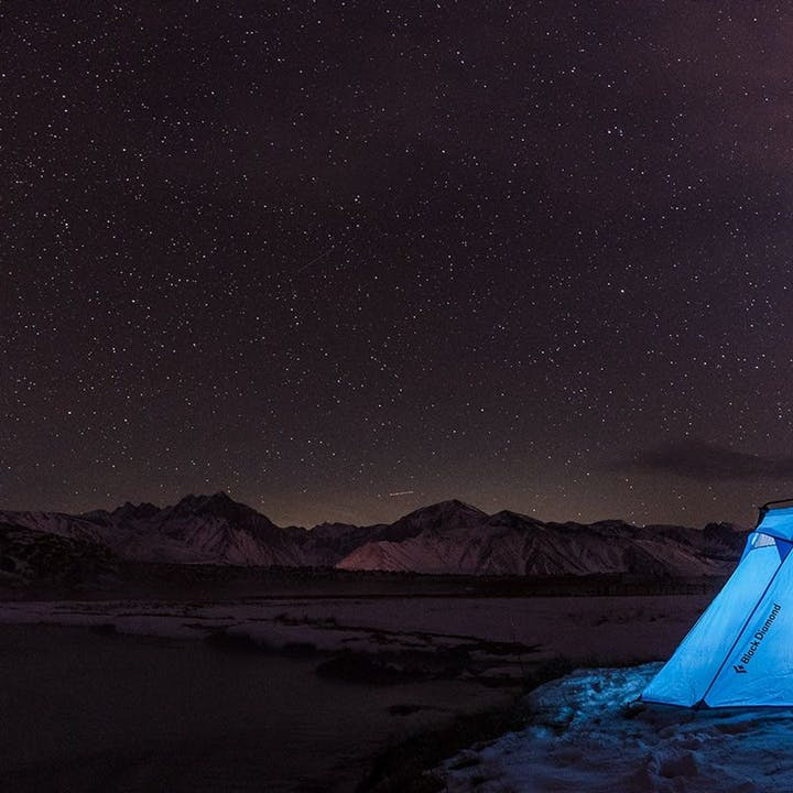 Photograph by Christian Adam of an illuminated tent at night