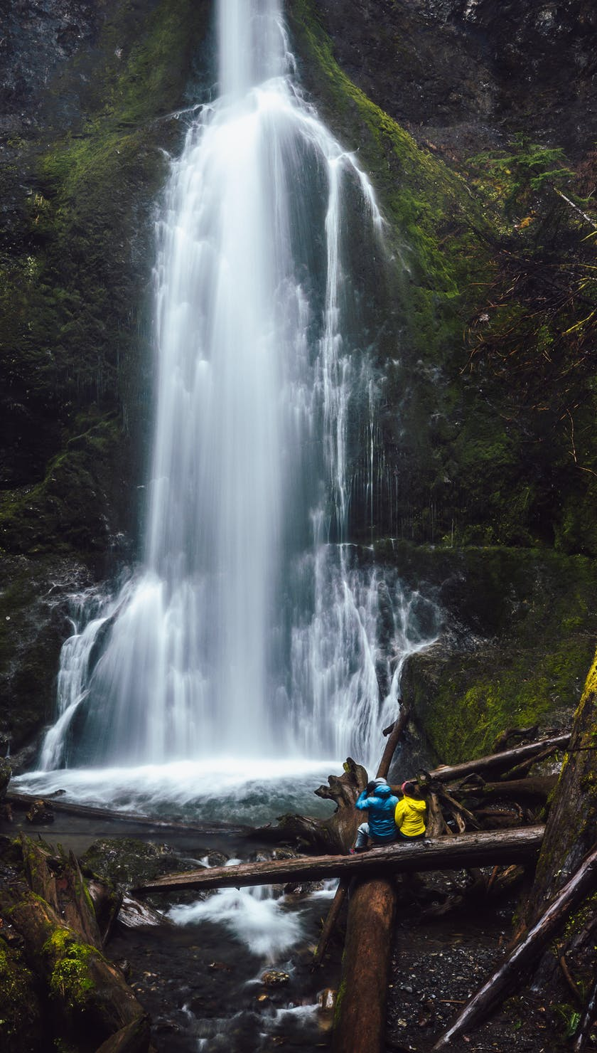 People wearing Black Diamond rain jackets near a waterfall
