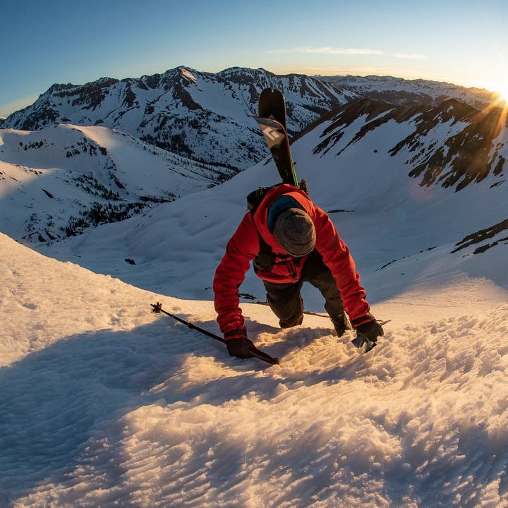 Photograph by Jeff Cricco of a man scaling a snowy mountain with skis on his pack