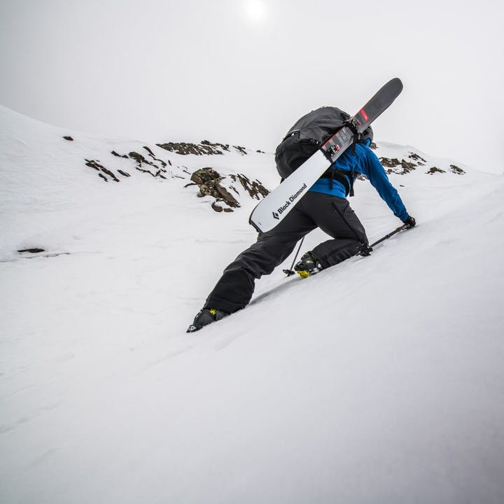 Photograph by Andy Earl of a person scaling up a snowy mountain with skis on their pack