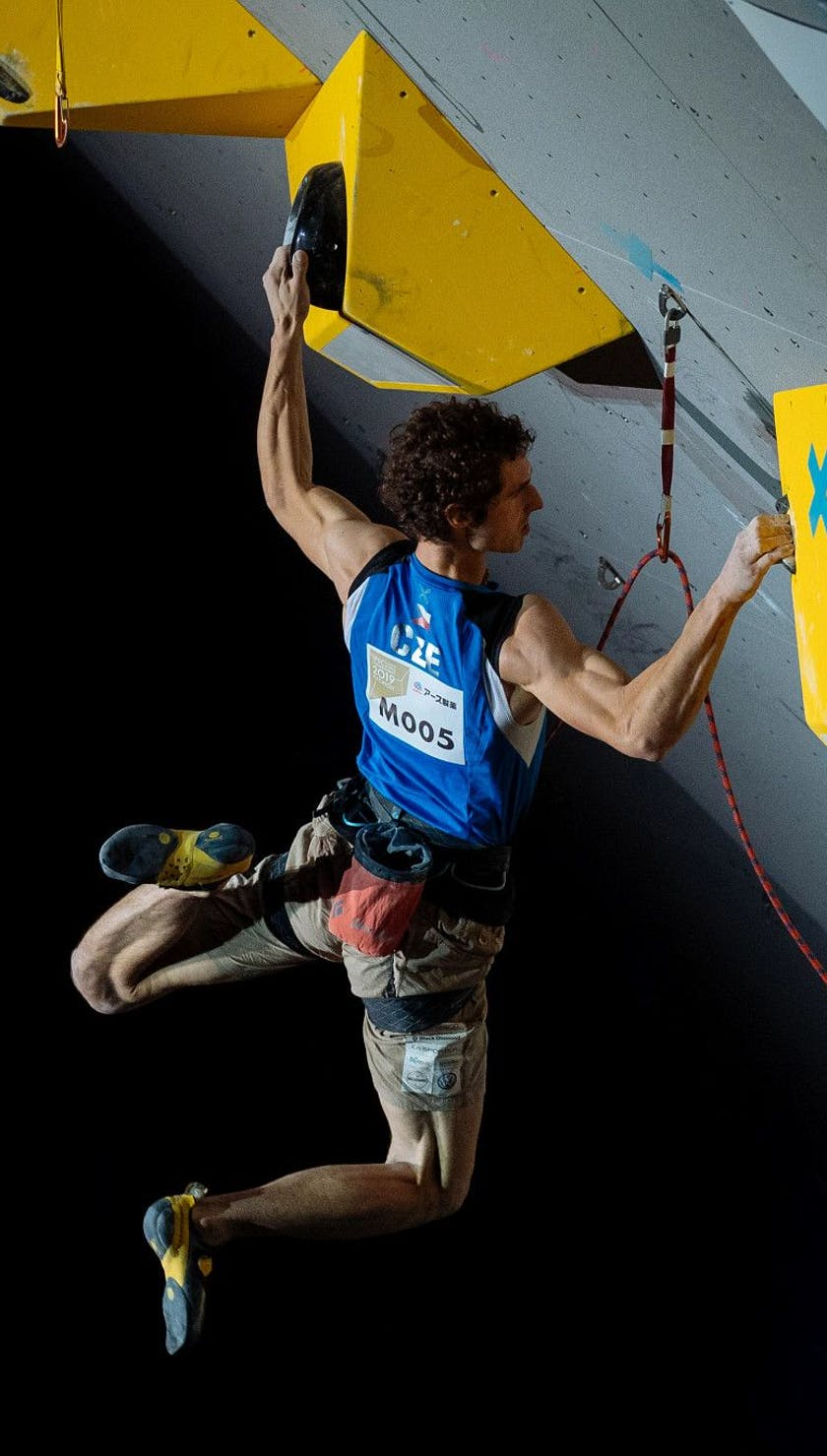 Adam Ondra wearing the Airnet Harness while climbing in a sport climbing competition