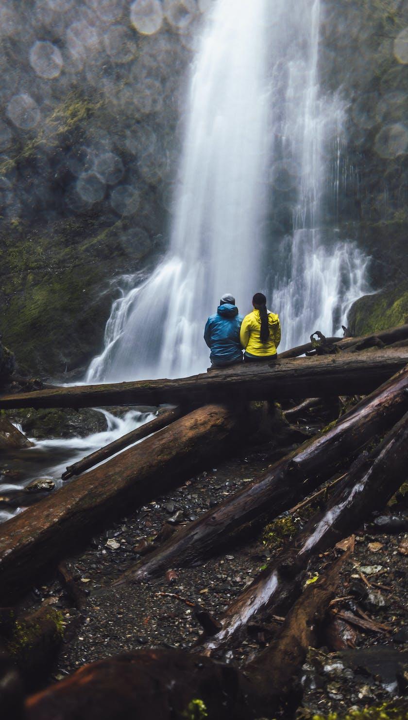Outdoors enthusiasts testing black diamond rainwear at a waterfall